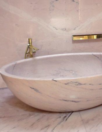 """Bagno padronale realizzato con pregiati marmi in tonalità rosa, l'elegante vasca da bagno ovale è un elemento scolpito in unico blocco. [wp-svg-icons icon=""""search-2"""" wrap=""""h1""""]"""