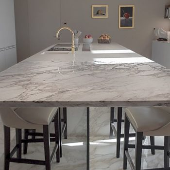 """Il marmo """"calacatta oro"""" è il materiale scelto per la realizzazione del piano e del pavimento di questa luminosa cucina. [wp-svg-icons icon=""""search-2"""" wrap=""""h1""""]"""