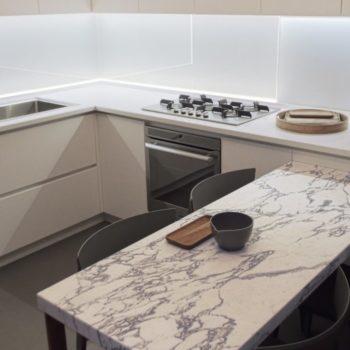 """Per questo ambiente cucina accogliente sono stati realizzati un piano tavolo in marmo Arabescato e un piano cucina in Okite bianca. [wp-svg-icons icon=""""search-2"""" wrap=""""h1""""]"""