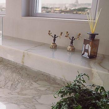 """Per un lussuoso attico in Roma, Damiani Marmi ha realizzato l'intero ambiente living. La pavimentazione e gli elementi d'arredo sono pezzi unici. Realizzato un esclusivo elemento d'arredo in marmo retroilluminato. [wp-svg-icons icon=""""search-2"""" wrap=""""h1""""]"""